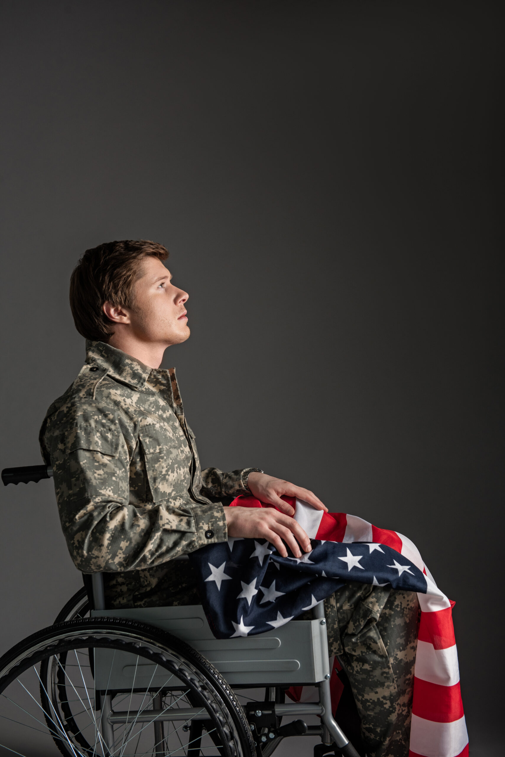 American Military Veteran Sitting in Wheelchair, Wearing Camouflage and Holding United States Flag