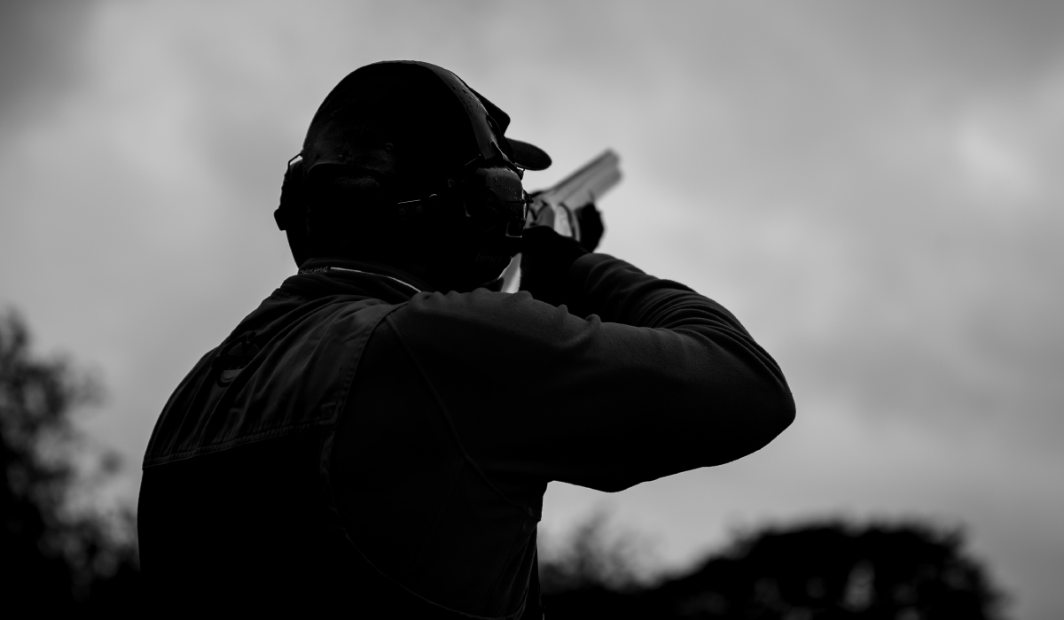 Over-the-shoulder View of Skeet Shooter Holding Shotgun, Aiming Upward