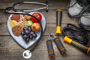 A heart-shaped plate of nuts, fruit and vegetables next to a stethoscope and various fitness equipment