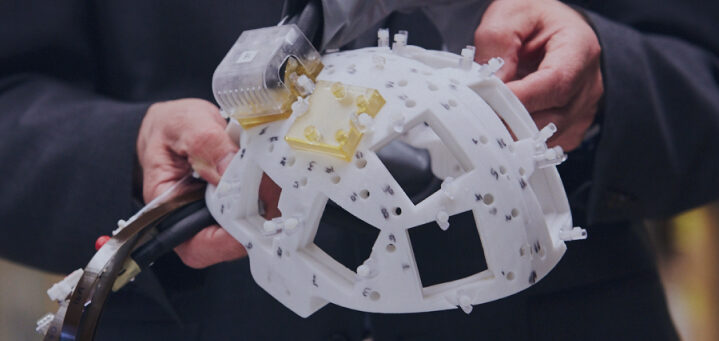 A person holding a wearable device for tracking brain activity
