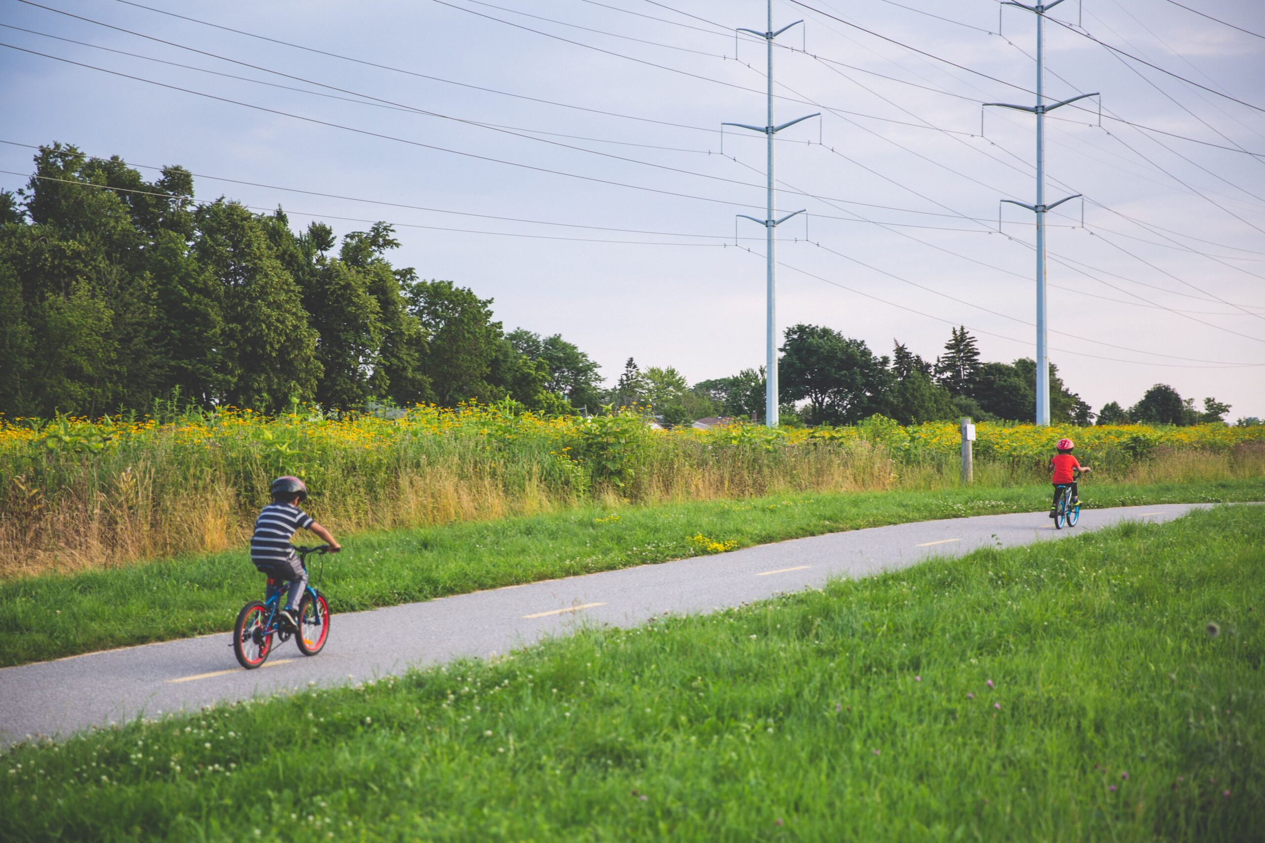 Two children cycling on a bike path