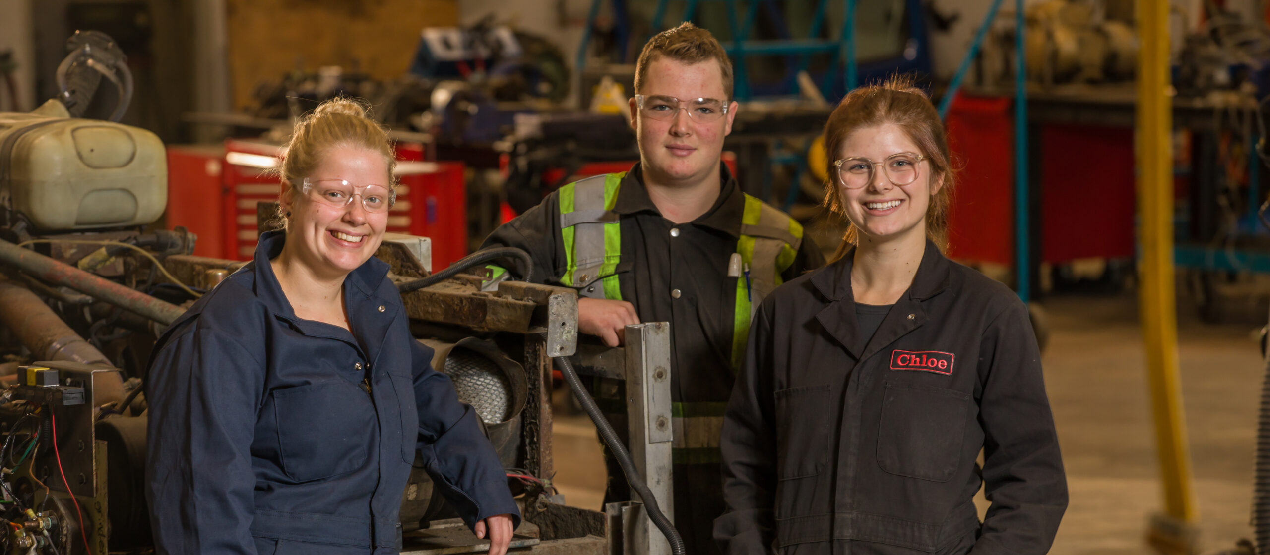 Three smiling people in a workshop