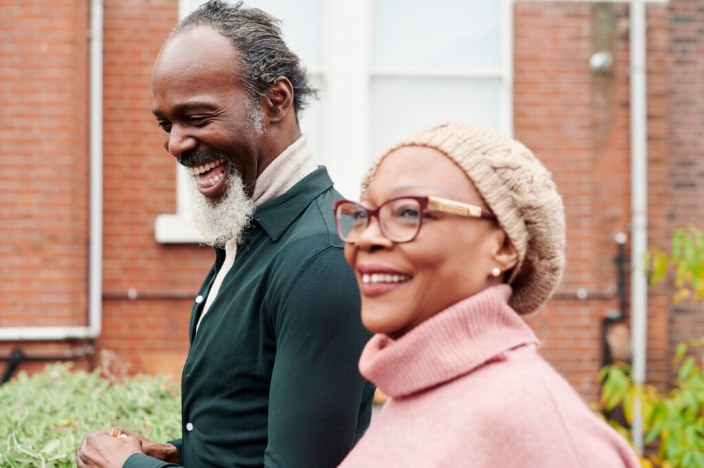 Senior African American woman laughing while going for a walk outside with her adult son