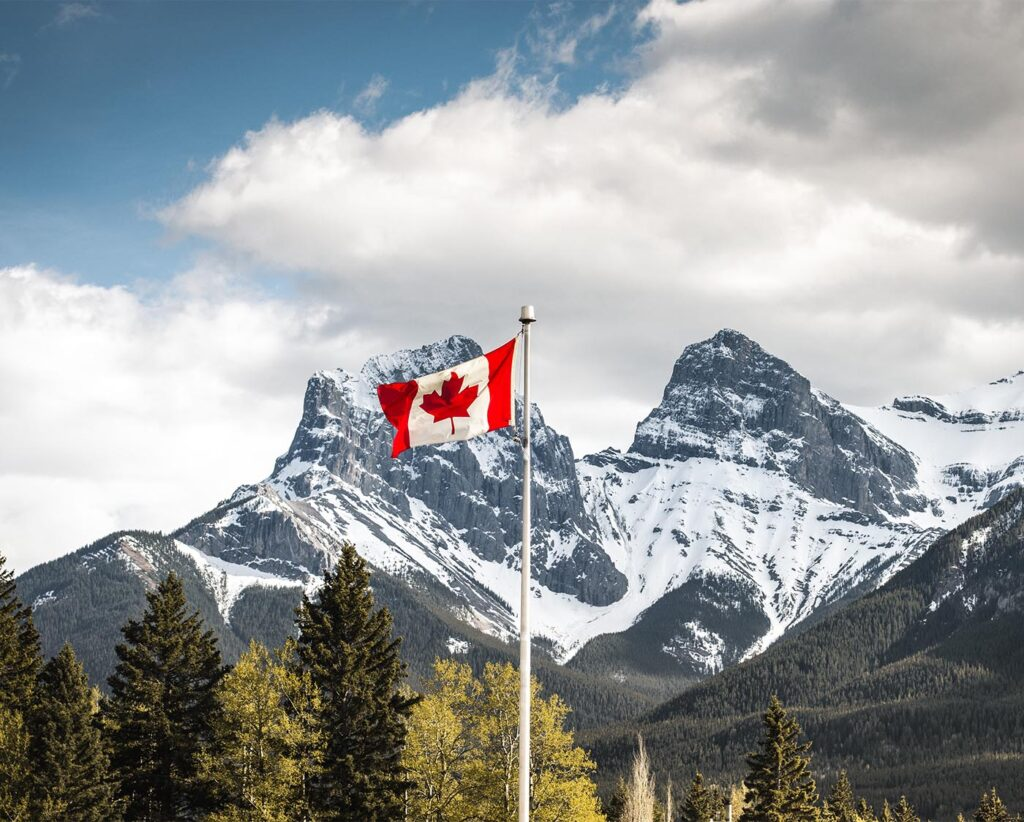 Landscape photograph of snowy mountains with the Canadian flag in the foreground