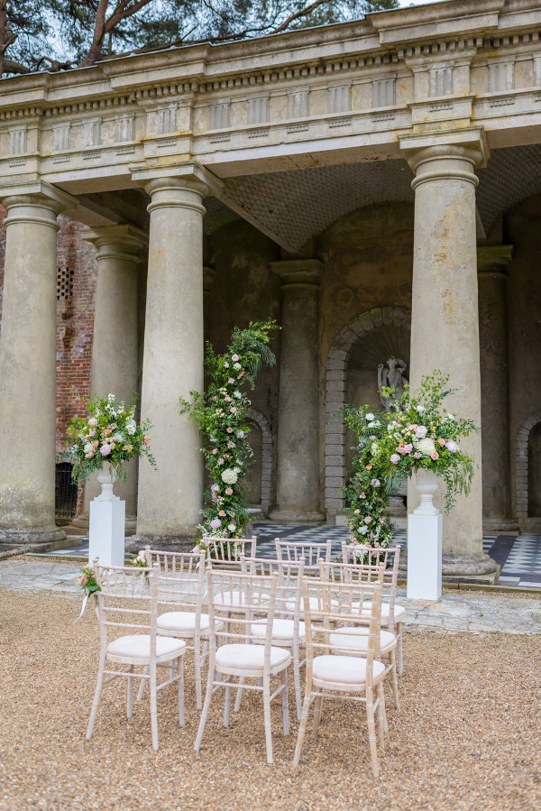Outdoor wedding ceremony with asymmetrical arch and pillar flower arrangements
