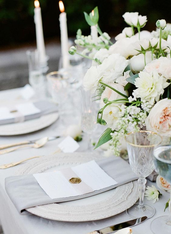 Wedding table set with glasses with gold rims, grey napkins, blush and cream flowers and candles