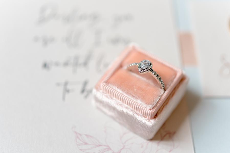 Diamond engagement ring sitting in blush pink velvet ring box