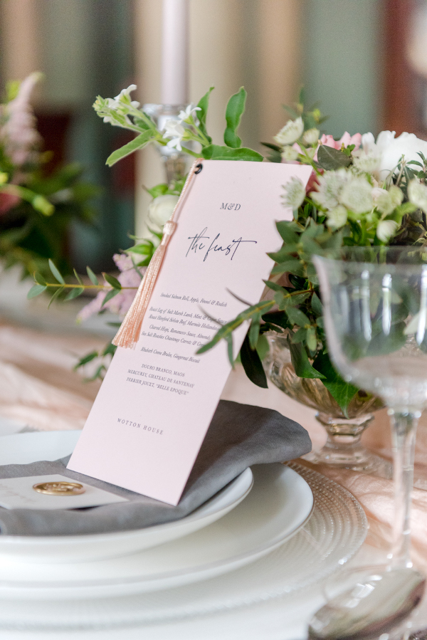 Wedding reception table setting with napkins, menu, crockery, cutlery and glassware