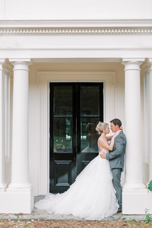 Bride & groom posing outside door to garden of Morden Hall, historic wedding venue in London.  Georgina Alexander Weddings Luxury Surrey Wedding Planner UK