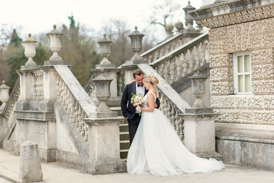 bride and groom standing on the steps of Chiswick House