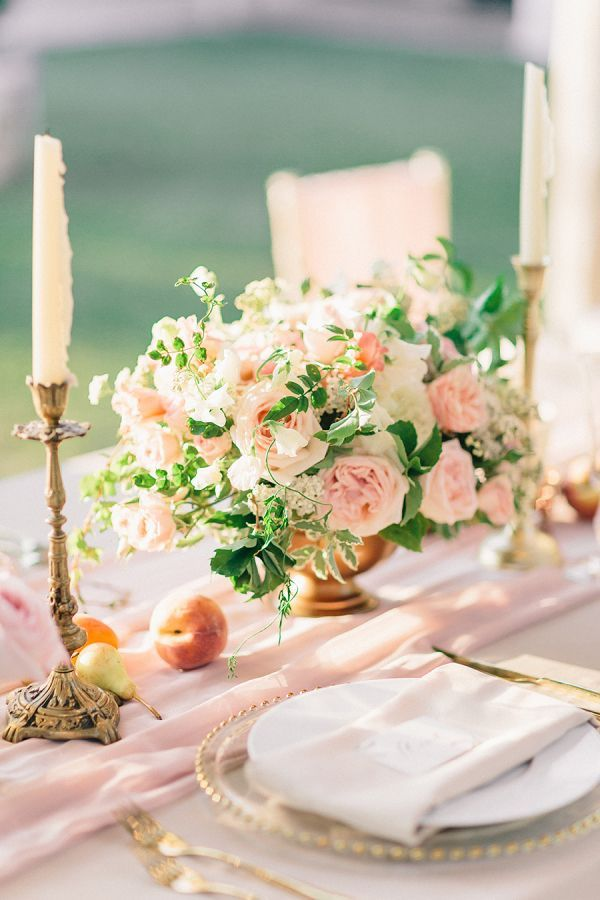 Wedding reception table set with peach and lemon floral centrepieces