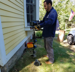 A man usign a drill to dig holes for termite bait stations.