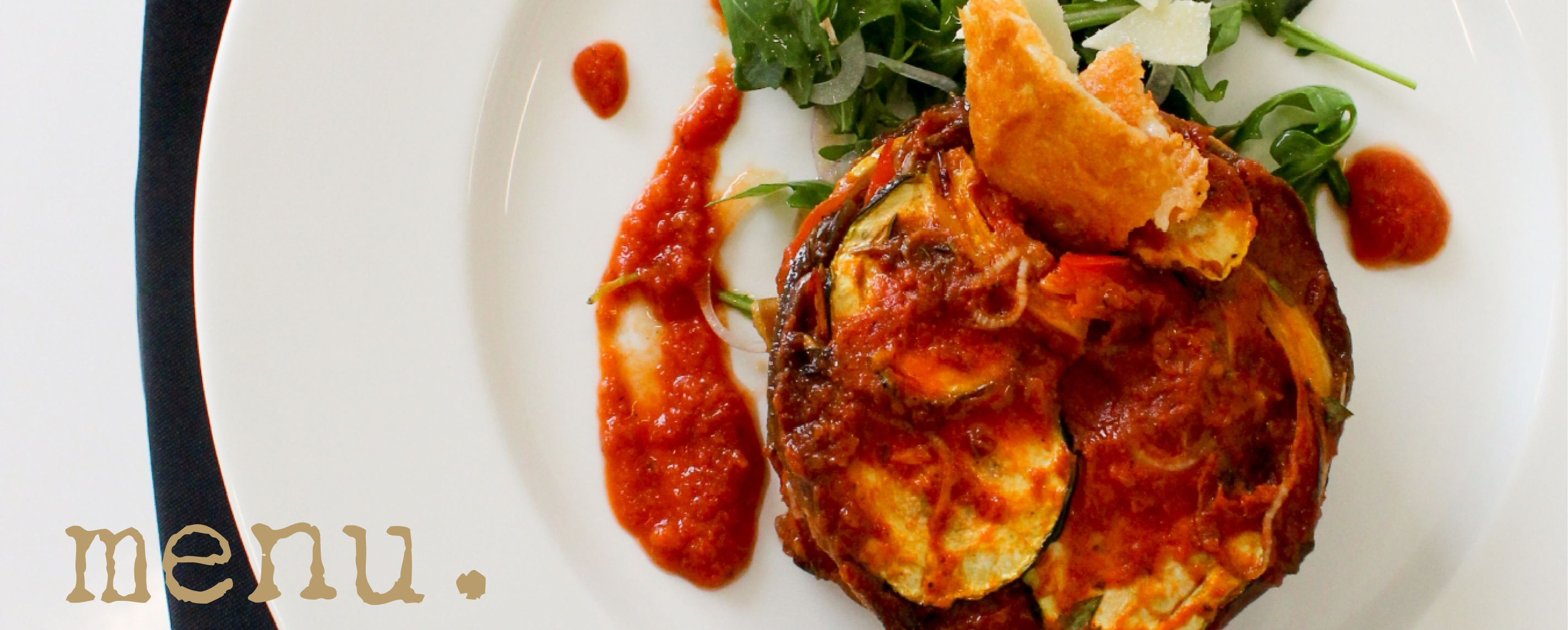 Ratatouille - A delicious blend of seasonal vegetables baked in a zesty arrabbiata sauce. Served over garden fresh arugula tossed in a lemon vinaigrette topped with a parmesan tuile