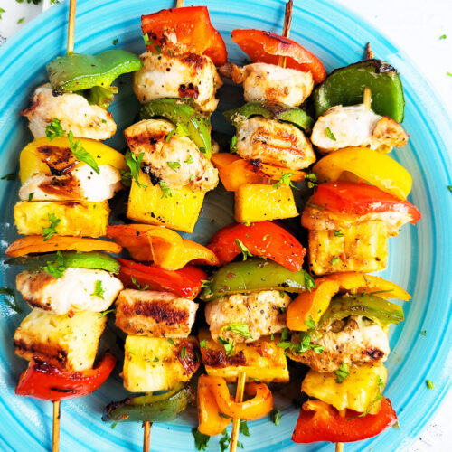 Make this Memorial Day weekend the best one yet with these super fun Hawaiian Grilled Chicken & Pineapple Kabobs made with red bell peppers, green bell peppers, yellow bell peppers and orange bell peppers, pineapples, and chicken. littleeatsandthings.com