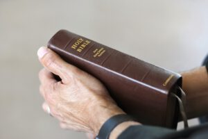 Holding a Bible.