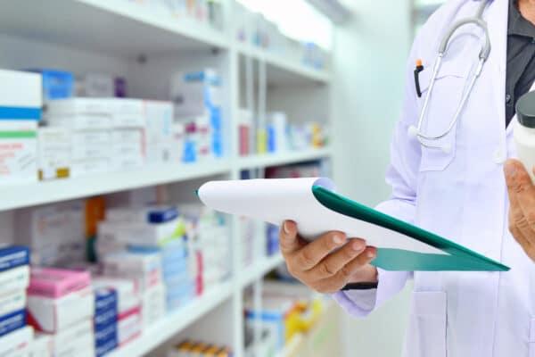 Pharmacist_holding_medicine bottle and computer tablet for filling prescription_in_pharmacy_drugstore