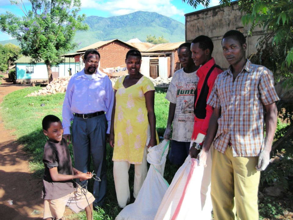 Some our kids and the a local pastor holding bags of rice donated by a local Christian group