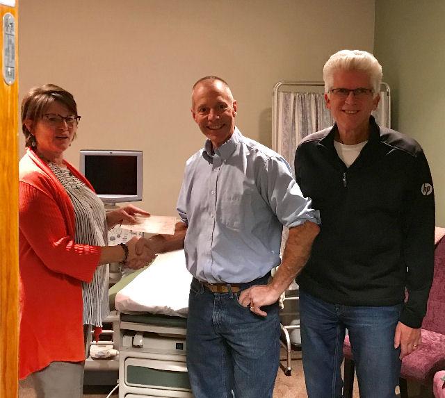Joe Gerke and Financial Secretary John Thayer present Baby Bottle Boomerang check to HELP director Paula Veneklause.