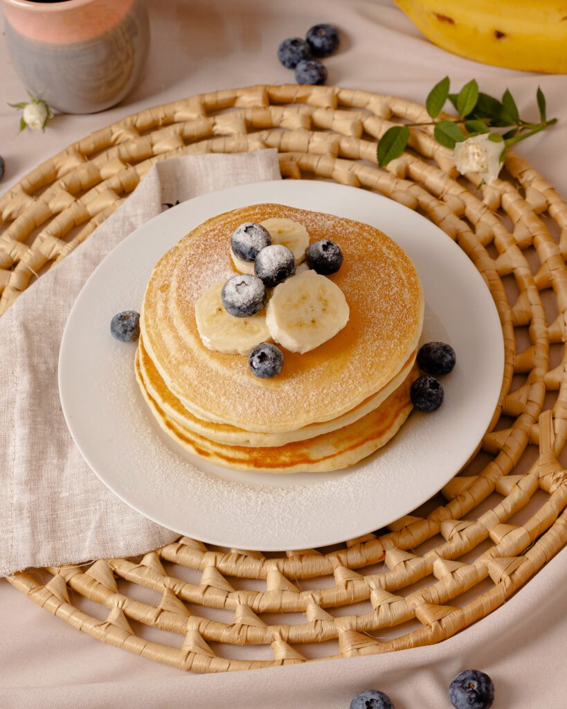 Pancakes topped with sliced bananas and blueberries