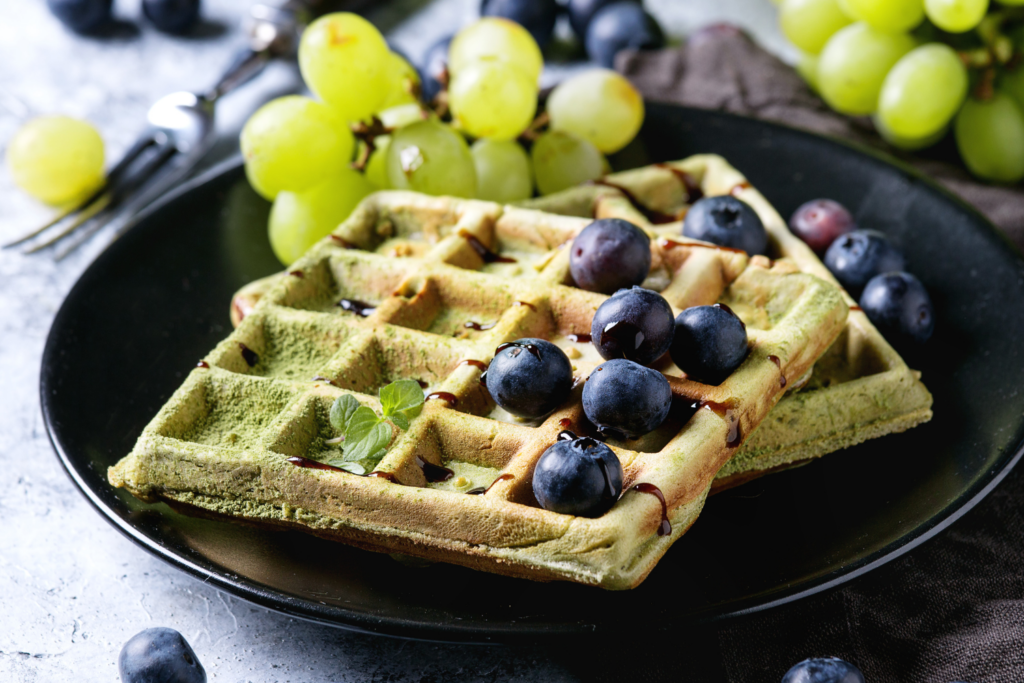 Square Green Waffles on a plate with grapes and blueberries