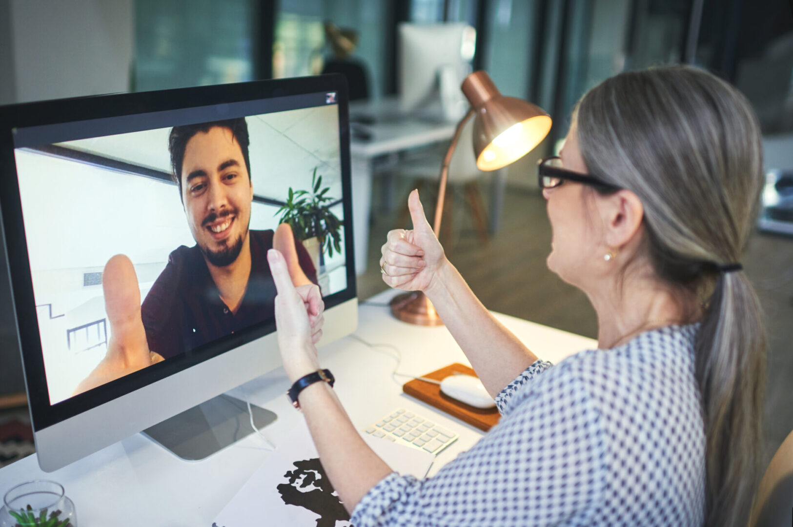 Shot of a young man showing thumbs up during an online counselling session with a psychologist