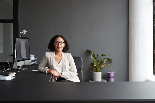 Portrait of smiling businesswoman sitting at modern office desk