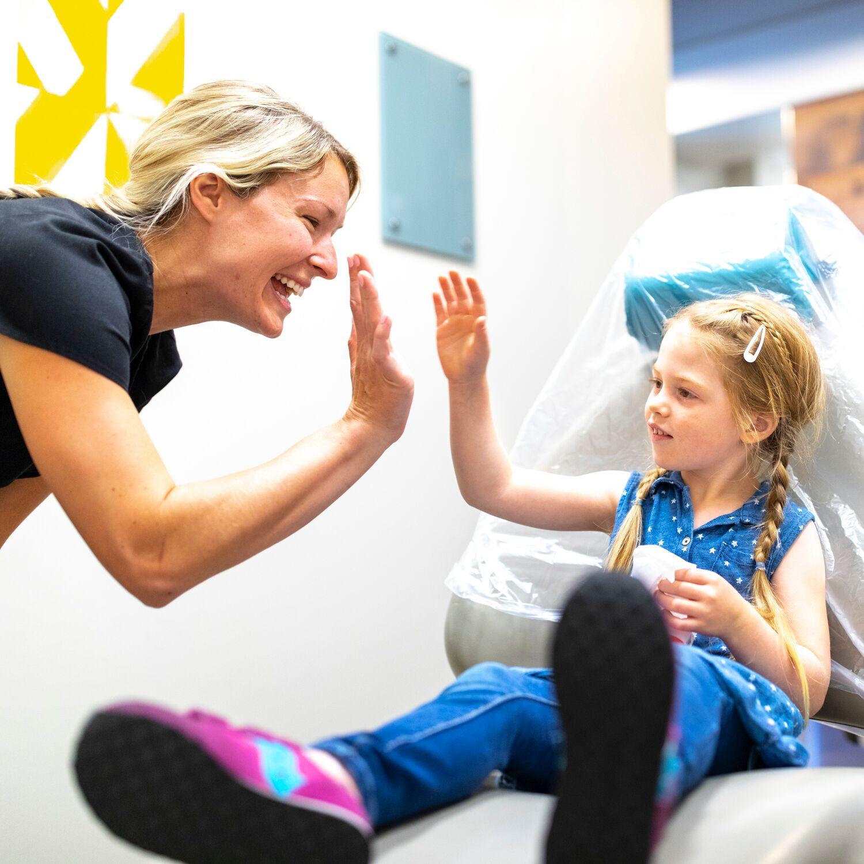 dental assistant high fiving child