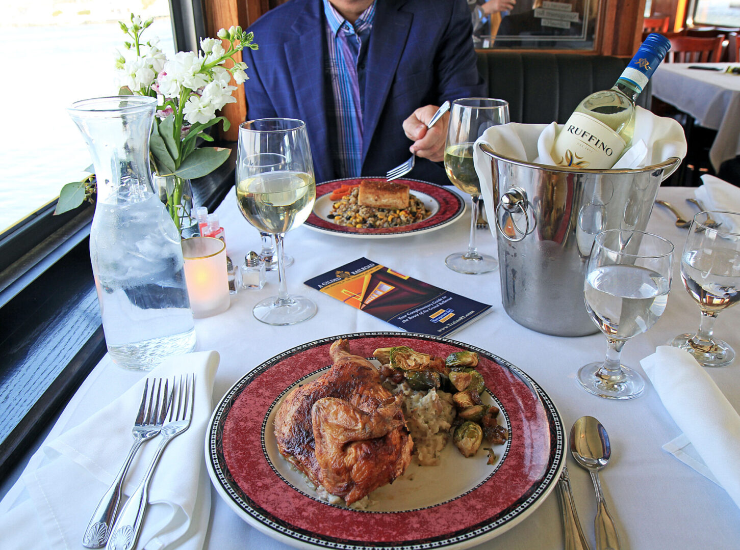 guests enjoying beautiful chicken and fish meals at the Grand Bellevue train