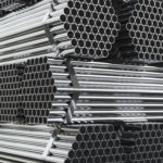 Stack of steel pipes in warehouse. Rolled metal products. 3d illustration.
