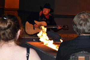 A man playing a guitar by the campfire