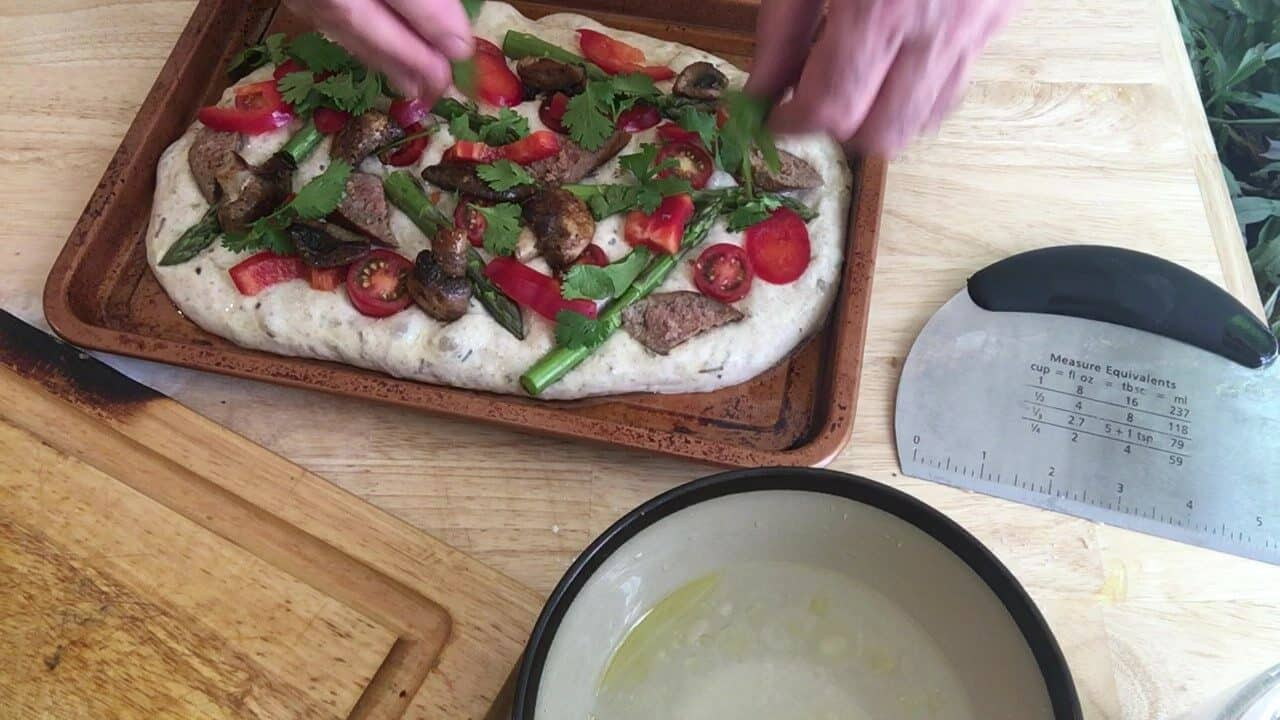 adding toppings to focaccia