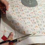 Cutting out circular DIY reusable beeswax wrap from fabric.