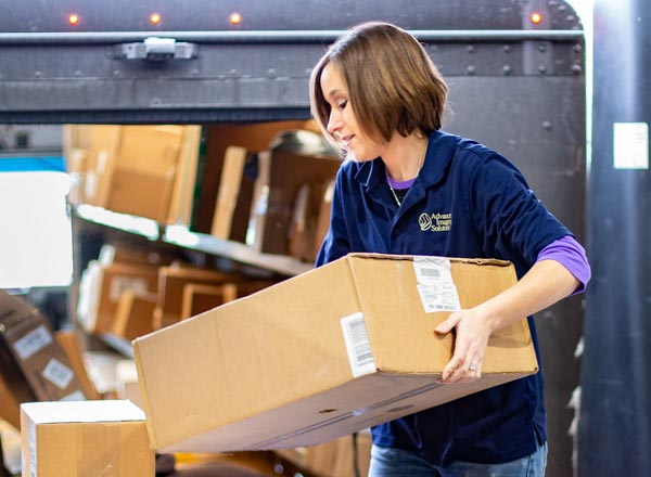 Female employee unloading packages from a truck