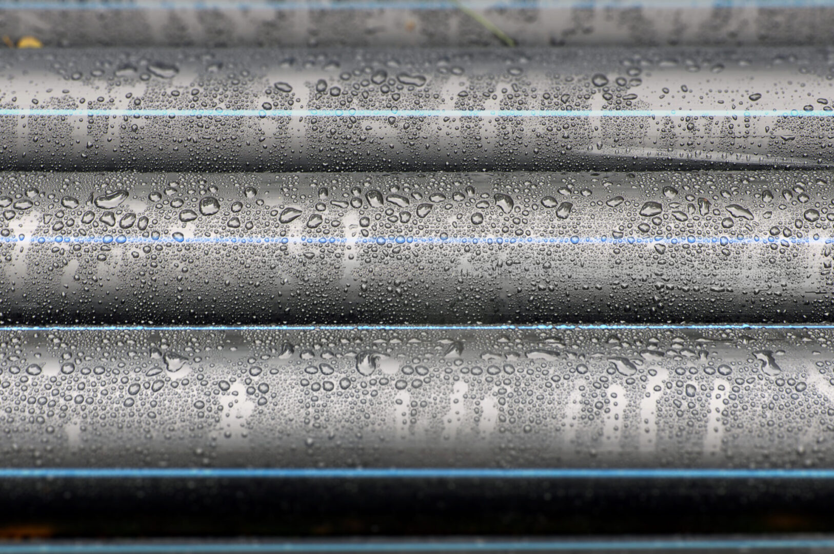 Many industrial black plastic pipes with water drops close-up in perspective.