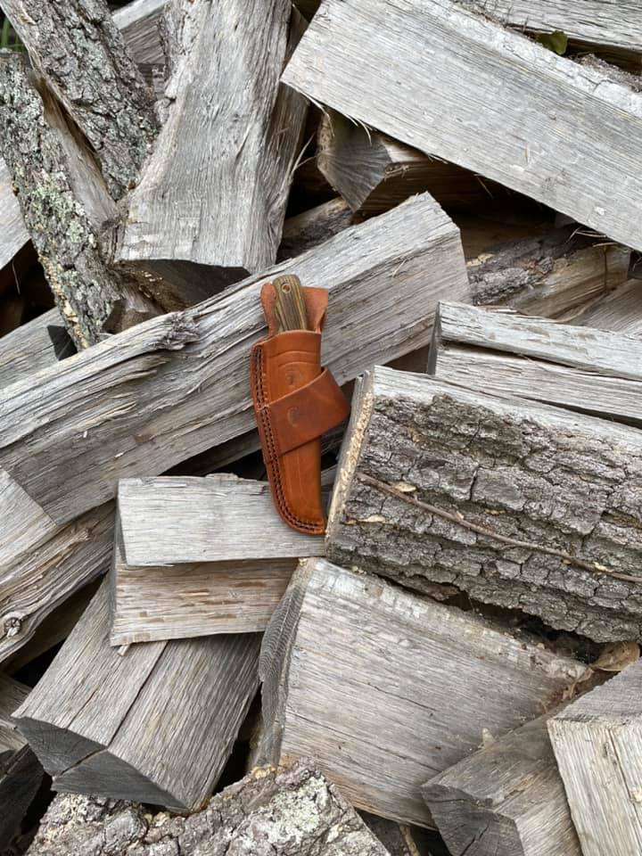 knife in leather case on wood pile