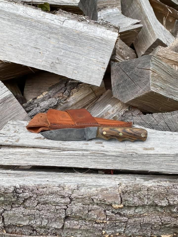 Alaskan hunter bush knife on wood pile