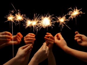 different hands holding sparklers