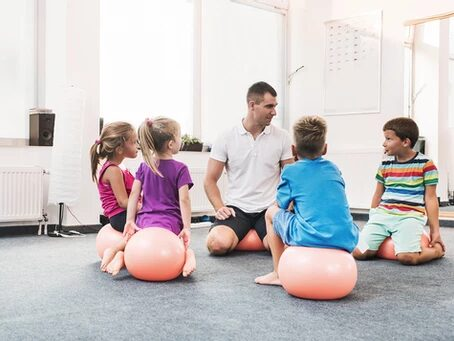 an adult and four children sitting on exercise balls