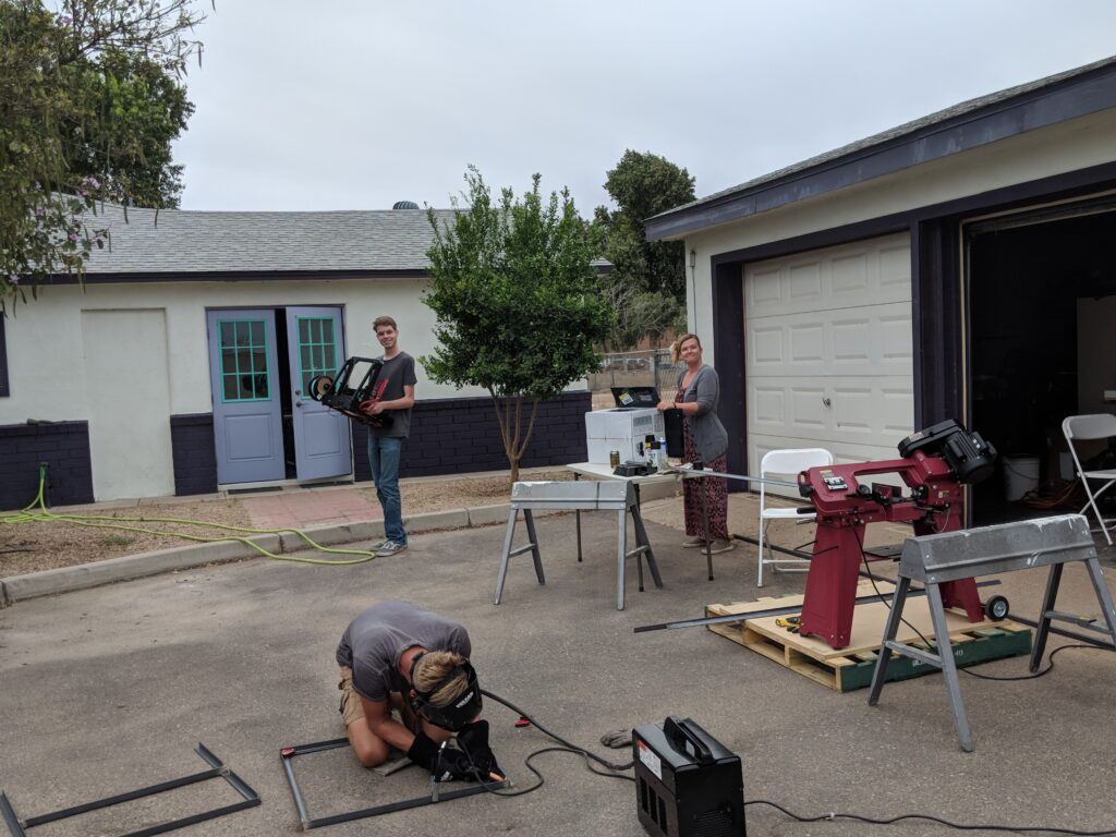 folks standing outside while working on a welding project
