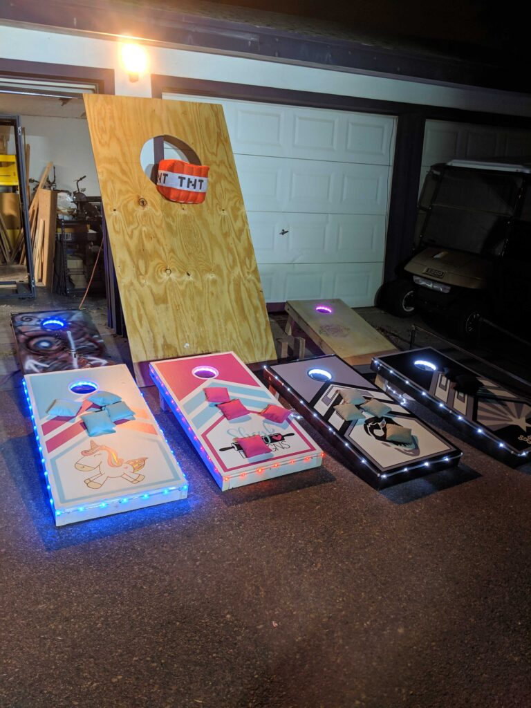 several different cornhole boards all lined up after judging.