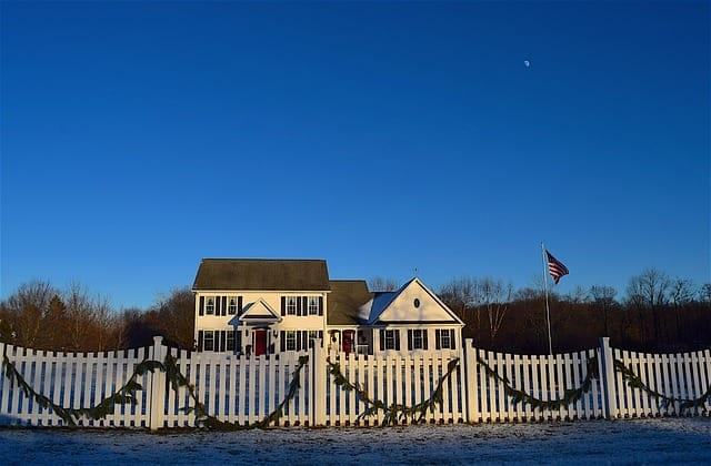 Big home with a white picket fence out front.