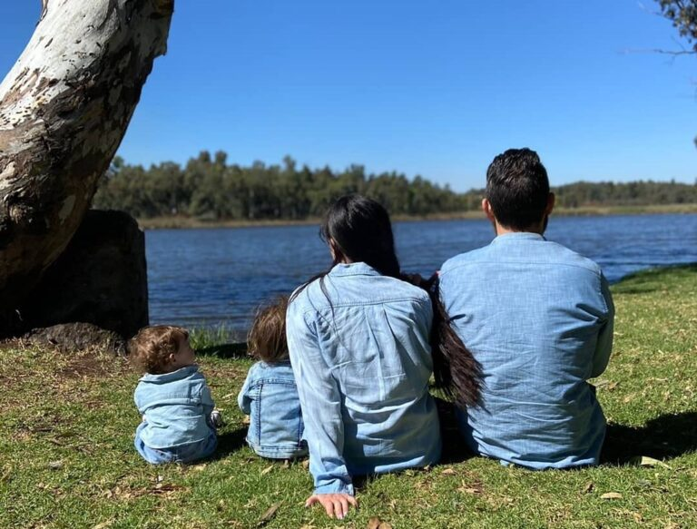 family sitting under the tree by water