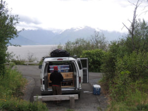 a campsite in Alaska with a Camper Van parked