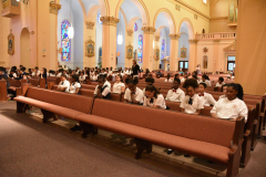 Students sitting at pews inside chapel.