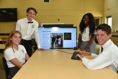 students at computer screen looking at camera