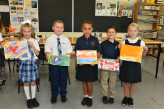 students showing off their artwork