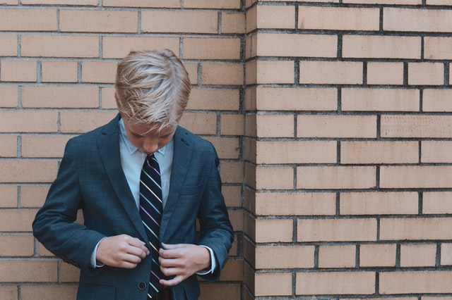 child putting on a suit standing in front of a brick wall