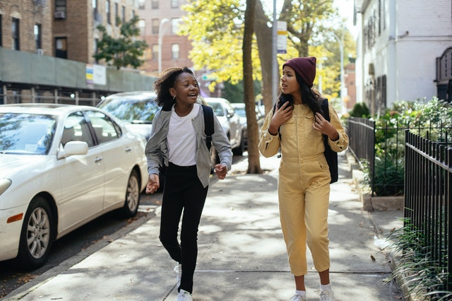 two preteen girls talking while walking on city street
