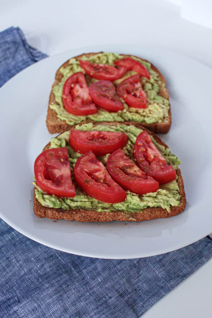 Toast with smashed avocado and sliced tomato