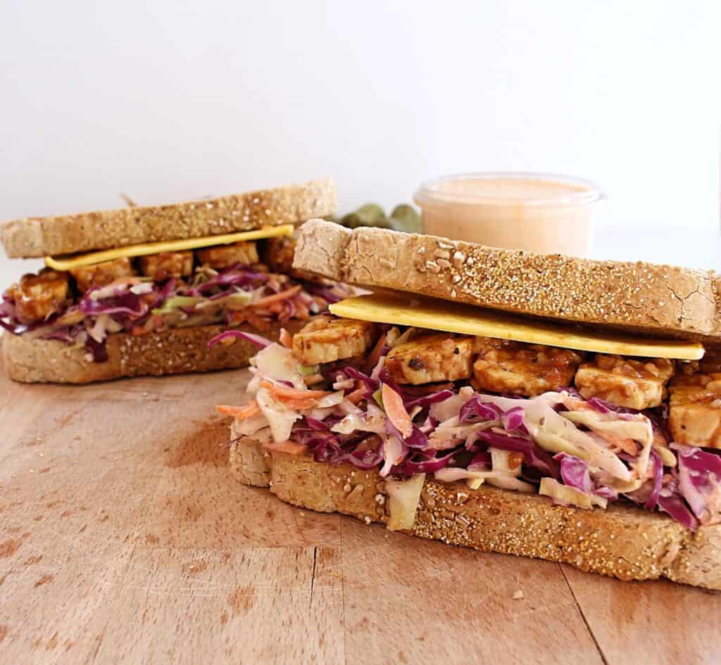 A ready-to-eat tempeh reuben sandwich with coleslaw served on a wooden cutting board